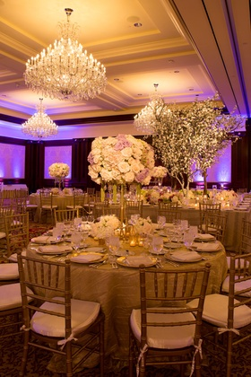 Ballroom wedding reception with tall flower arrangements and cherry blossom tree decorations
