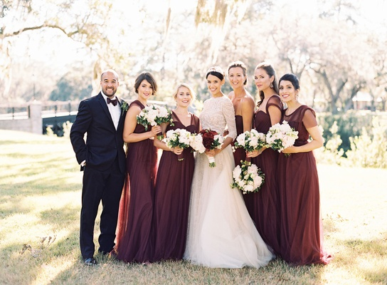 Bride in long sleeve lace wedding dress with five bridesmaids in long burgundy dresses sleeveless