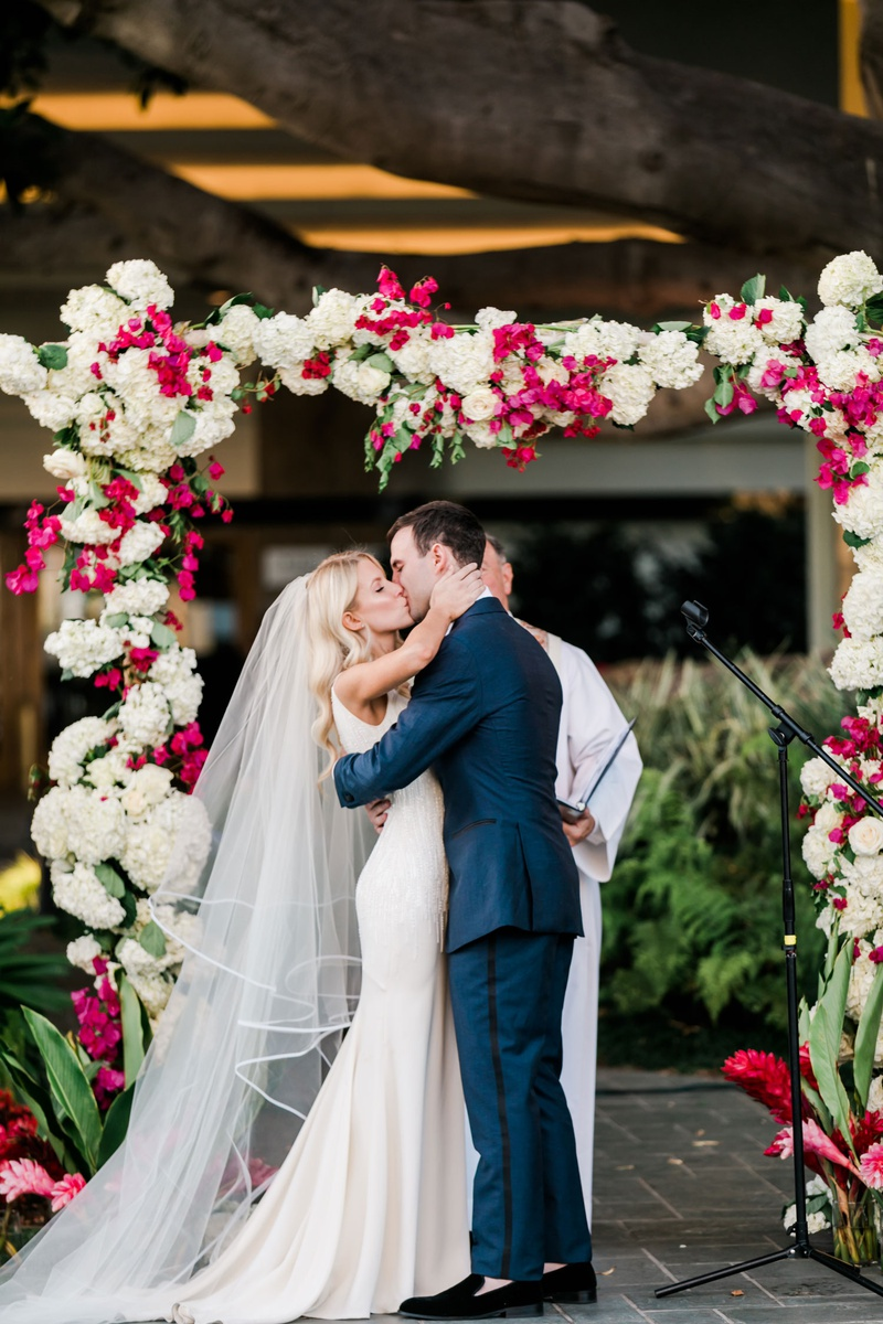 bride kisses groom at outdoor ceremony under fig tree arch with white hydrangeas pink bougainvilleas