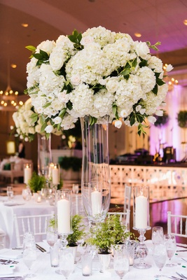 Clear glass riser with white arrangement of hydrangea flowers, rose, tulip and green leaves