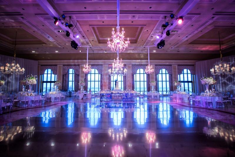 Wedding reception set up at The Breakers ballroom purple lighting, chandeliers, candelabra, white