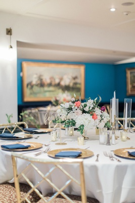 Round wedding reception table gold chairs gold charger plate navy blue napkin to match walls