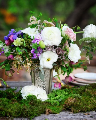 Outdoor wedding reception table with moss and silver vase with white, pink, purple, and green flower