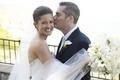 Groom kisses bride on cheek on wedding day