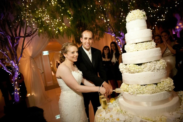 Bride and groom cut into towering wedding cake