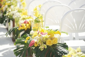 White ceremony chairs and jungle leaf decorations