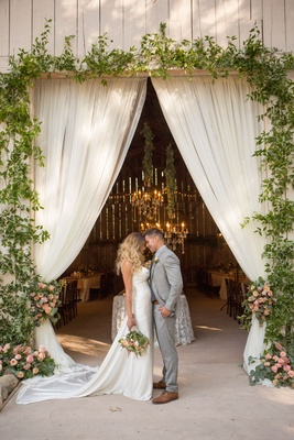 Bride in Ines Di Santo silky wedding dress groom in grey suit hair down curls drapery barn greenery