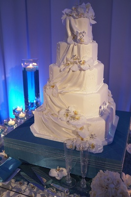 white cake decorated with fondant ribbons and white orchids