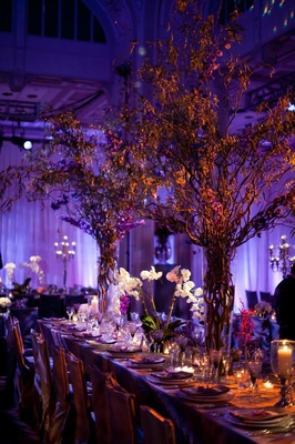 Purple lighting at wedding reception with branch flower arrangements