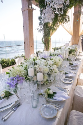 Wedding reception long table with candles pillar with white flower arrangements chandeliers overhead