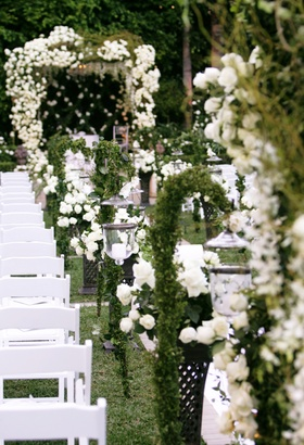 The aisle of a garden ceremony was decorated with greenery and white roses