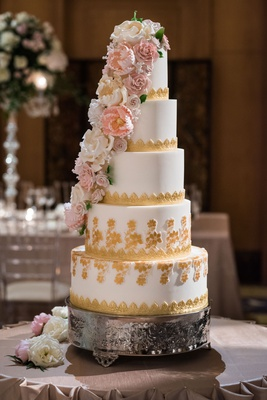 wedding cake five layers with gold details and pink white sugar flower down side of cake