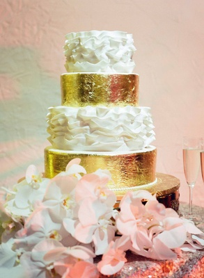Wedding cake with gold leaf and white ruffles next to phalaenopsis orchids