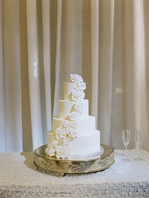 four layer white fondant wedding cake on stand with sugar flower roses going down side