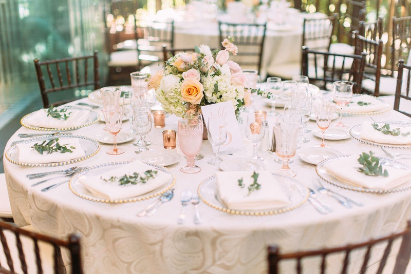 wedding reception round table wood chair low centerpiece pink antique crystal goblets greenery plate
