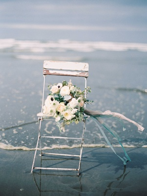 a bouquet of white and green with blue ribbons on an old wooden chair on the beach