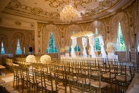 Wedding ceremony indoor ballroom chandelier white flowers ceremony arch