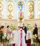 traditional wedding ceremony pretty church greenery white flowers on pews bridesmaids groomsmen