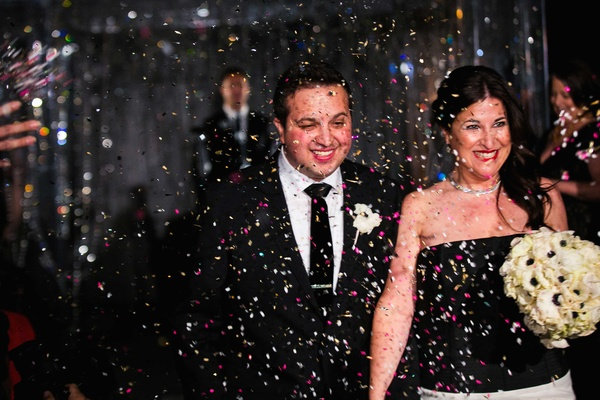 a newlywed groom in a black tuxedo and bride in a black and white gown walk through confetti