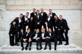 Groom and groomsmen ring bearers family on marble steps at wedding venue