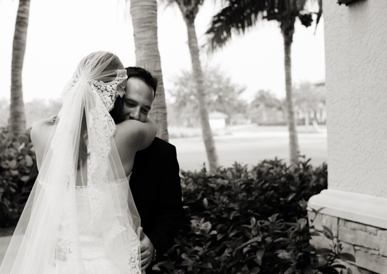 Black and white photo of bride hugging groom in veil
