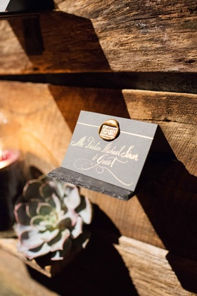 Grey escort card with gold calligraphy and wax seal on barn wood wall at rustic reception