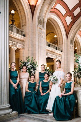 bride in mother's wedding dress with bridesmaids in high neck emerald gowns christmas new year