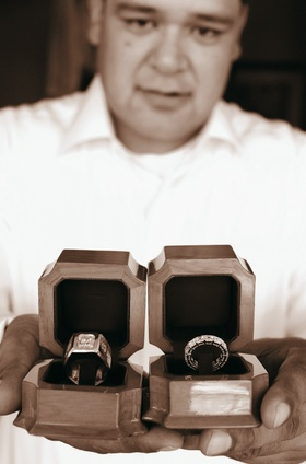 Sepia tone image of groom holding wedding ring boxes
