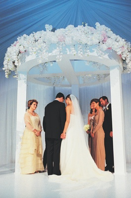 Bride and groom under white chuppah with white flower decorations