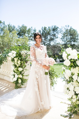 Bride's long sleeve Marchesa wedding dress with three dimensional flower appliques mark ingram
