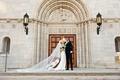 wedding portrait bride and groom kiss in front of church doors catholic church wedding