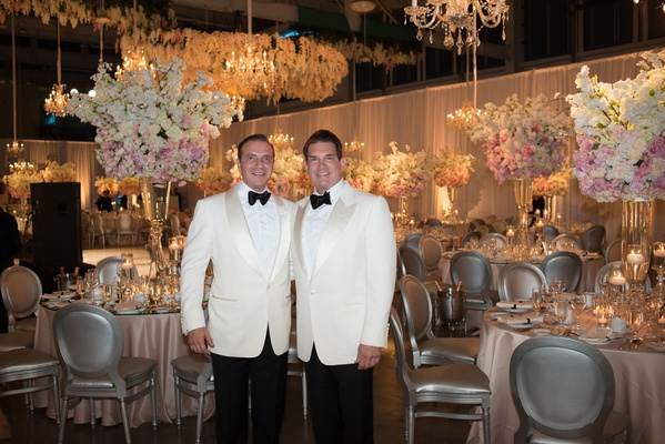 Grooms in alabaster tuxedo jackets black bow ties in reception space silver chairs pink linens