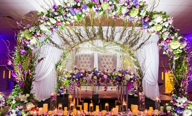 Wedding reception sweetheart table tufted chairs arch of flowers candles reception ideas purple