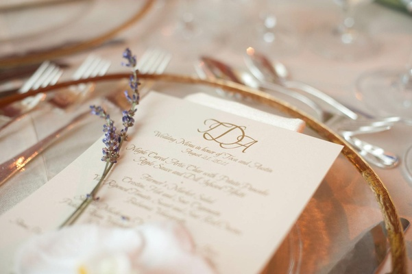 Gold-rimmed charger plate with menu and herb sprig