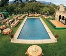 tables set up around swimming pool at estate