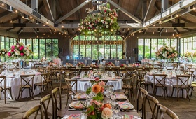 wedding reception wood beams twinkle lights flower chandelier pink orange flowers wood chairs