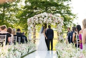 Bride in monique lhuillier wedding dress under flower arch groom white aisle runner pink ivory color