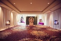 indian hindu wedding, gold statue of ganesha in front of wall of greenery, pictures of couple