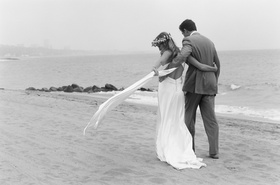 Black and white photo of bride and groom walking on beach