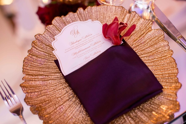 Gold texture charger plate on mirror table with die-cut wedding dinner menu inside purple napkin
