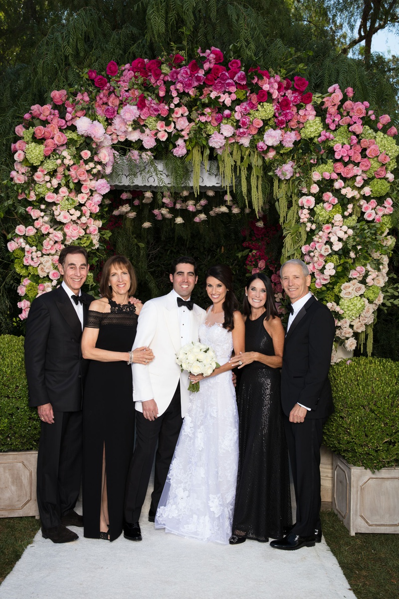 Wedding portrait bride and groom in white with parents under chuppah wearing black gowns tuxes