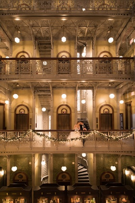 Bride and groom kiss on balcony above reception at brooklyn museum in new york