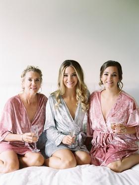 bride in grey velvet robe with sister and mom in dusty rose velvet robes, velvet getting-ready robes