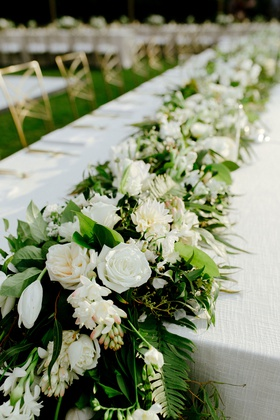 wedding reception white linen tablecloth with flower runner greenery fern tropical plants white rose