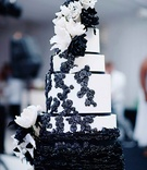 Black and white cake with ruffles, sugar flowers, and ribbons