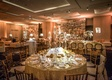 Wedding ballroom gold linens and chairs tall candle holders lounge seating mirror decor
