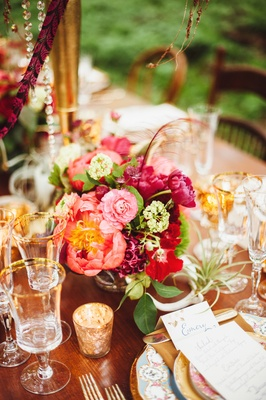 Wedding reception table with small bouquet of pink, red, and magenta flowers with a thin red feather