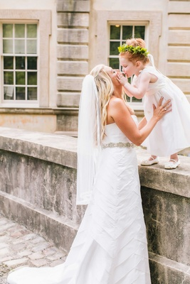 Bride in Anne Barge wedding dress kissing red head flower girl in white dress greenery floral crown