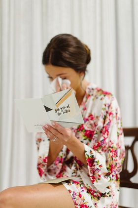 Bride in flower print robe crying while reading card see you at the altar from groom getting ready