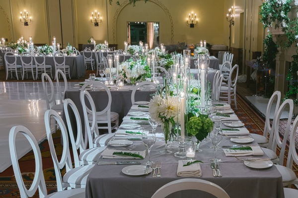 wedding reception, gray tables, white chairs with circle backs, tapered candles, green and white
